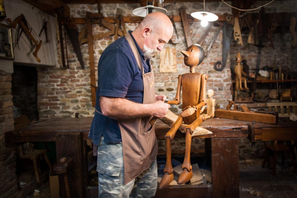 バルトルッチが木製玩具のピノキオを作成している